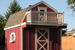 Storage shed with playhouse loft has an outdoor ladder that leads to a second story balcony