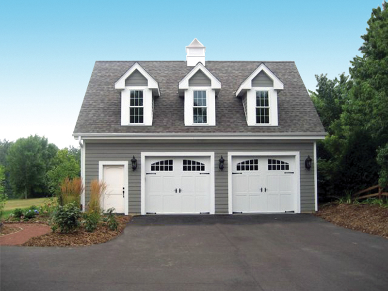 Two-car garage enjoys the Colonial style of three roof dormers and a handy entry door