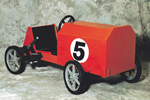 Children's wood coaster car is painted red with a racing number on the side