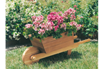 Whelbarrow planter is made of redwood cedar and holds many plants and flowers