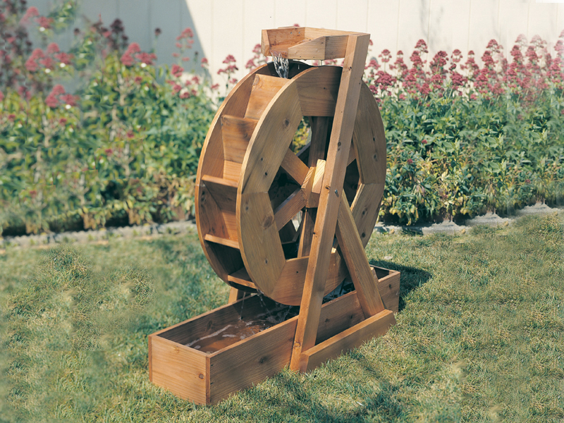 Wood water wheel adds charm to the backyard of a rustic or country house plan