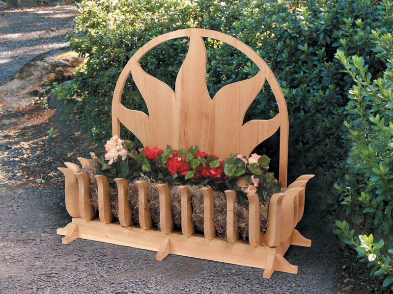 All wood ground level planter has sun shaped motif design on the back