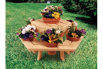Small hexagon wood picnic table holds multiple clay flower pots